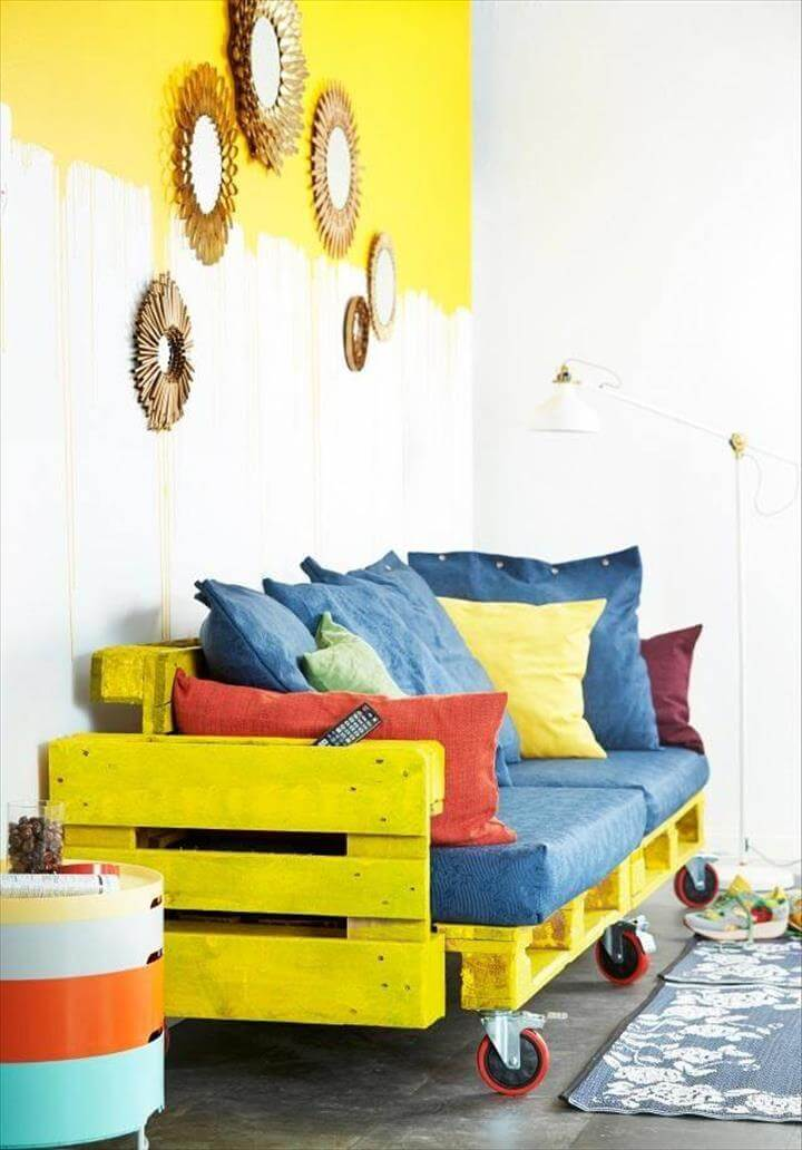 yellow painted pallet rolling sofa with blue cushion