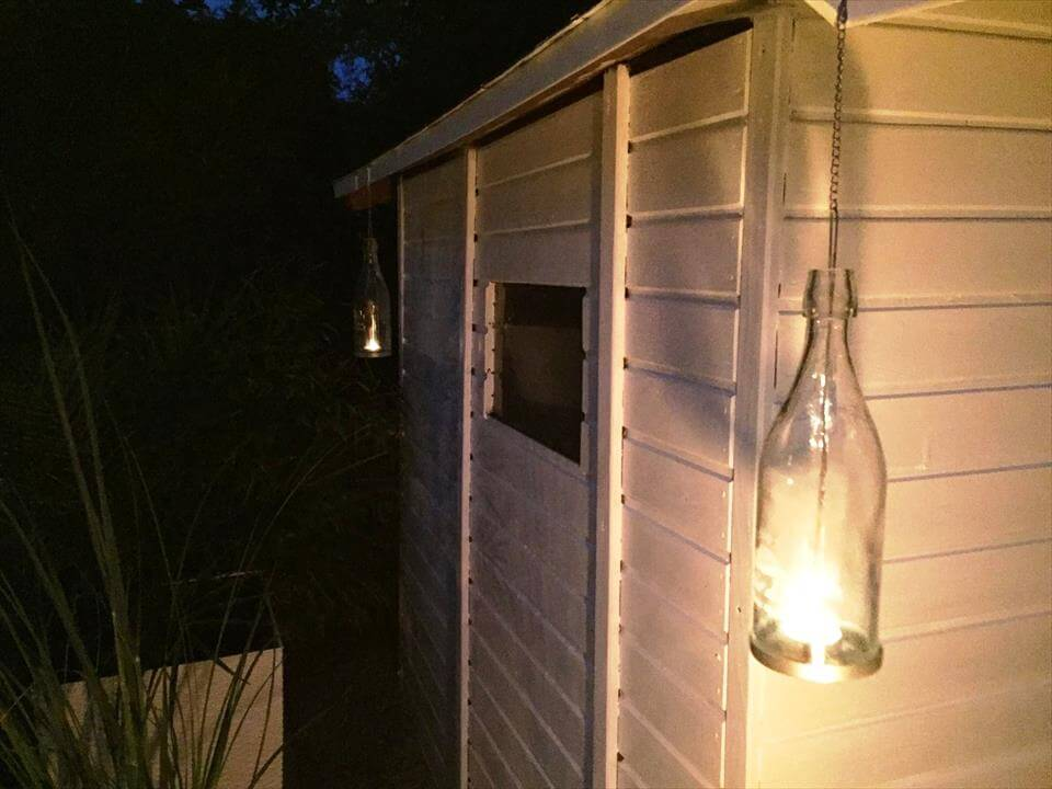 pallet wood shed with glass bottle hanging lamp