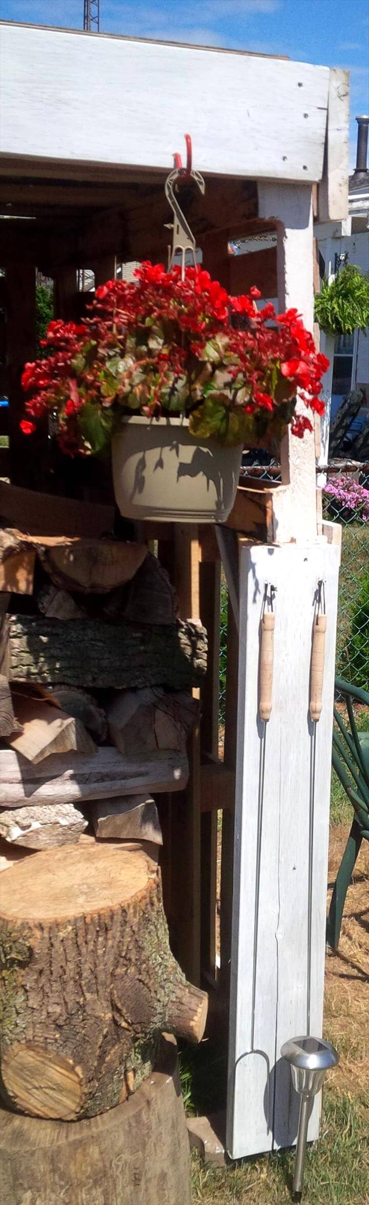 outdoor firewood shed with hanging flower planter