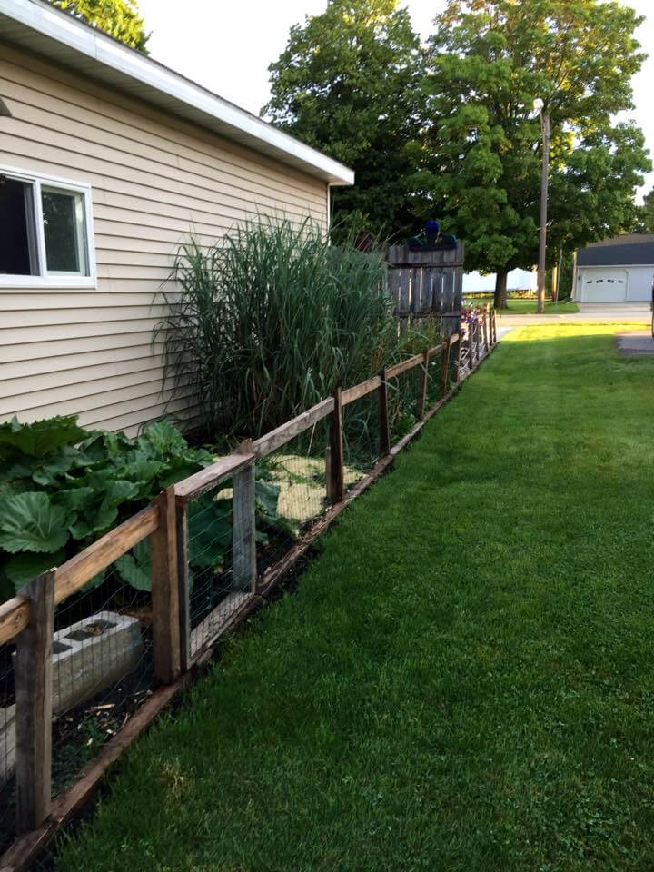 The fence is created with the pallet slat made squares filled with the ...